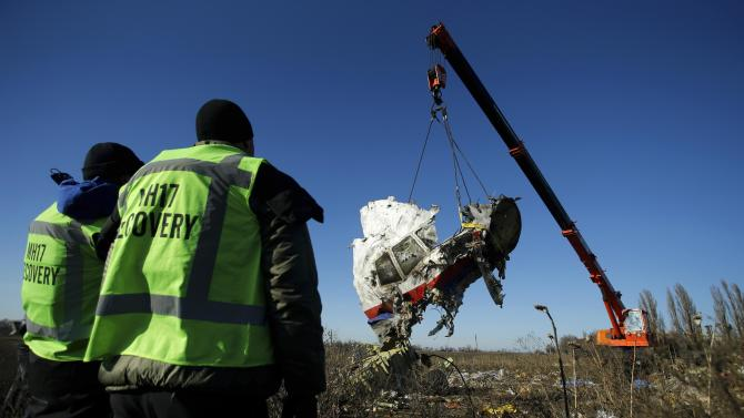 Investigators watch as a piece of wreckage from the Malaysia Airlines flight MH17 is transported at the site of the plane crash near the village of Hrabove (Grabovo) in Donetsk region