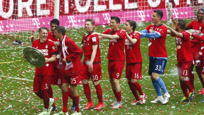 Bayern Munich's celebrate pose with the trophy after their final German first division Bundesliga soccer match of the season against FSV Mainz 05 in Munich