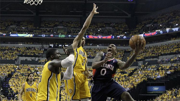Atlanta Hawks' Jeff Teague shoots against Indiana Pacers' Roy Hibbert and George Hill (3) during the first half in Game 1 of an opening-round NBA basketball playoff series on Saturday, April 19, 2014, in Indianapolis