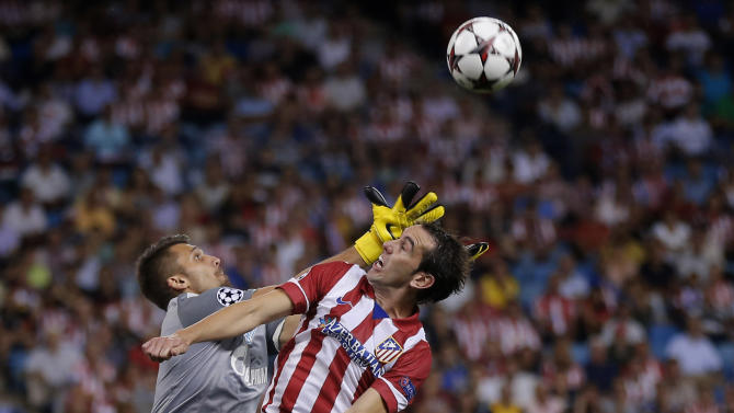 Atletico Madrid's Diego Godin from Uruguay, centre, duels for the ball with Zenit St. Petersburg's goalkeeper Yuri Lodygin during a Group G Champions League soccer match , at the Vicente Calderon stadium in in Madrid, Spain, Wednesday, Sept. 18, 2013