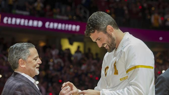 Cleveland Cavaliers' Kevin Love accepts his NBA championship ring from Cavaliers owner Dan Gilbert before a basketball game against the New York Knicks in Cleveland, Tuesday, Oct. 25, 2016. (AP Photo/Phil Long)