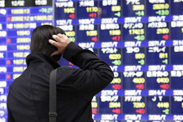 A man scratches his head as he looks at an electronic stock board of a securities firm in Tokyo Wednesday, Dec. 2, 2015. Asian stock markets were uneven Wednesday after weakness in U.S. economic data