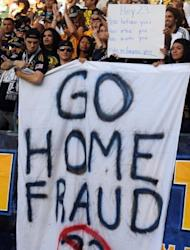 """LA Galaxy fans hold up a sign during a match in 2009 in a protest against David Beckham. Beckham's loans to European teams angered some LA fans who displayed their dislike with signs at games that said """"Go home fraud"""" and """"Part time player"""""""