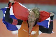 Michel Mulder from the Netherlands holds his national flag and celebrates winning gold in the men's 500-meter speedskating race at the Adler Arena Skating Center during the 2014 Winter Olympics, Monday, Feb. 10, 2014, in Sochi, Russia. (AP Photo/Matt Dunham)