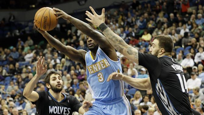 Denver Nuggets' Ty Lawson, center, squeezes between Minnesota Timberwolves' Ricky Rubio, left, of Spain, and Nikola Pekovic of Montenegro, in the second half of an NBA basketball game, Wednesday, Nov. 27, 2013, in Minneapolis. Lawson led the Nuggets with 23 points in the Nuggets' 117-110 win