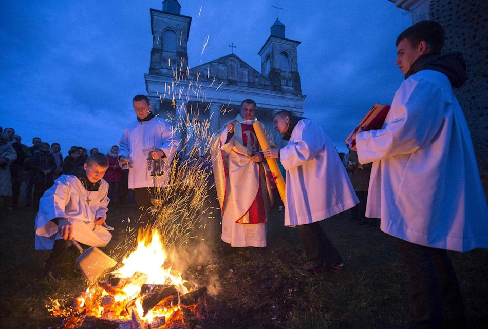 A Catholic priest and believers take part in a service on the eve of Easter Sunday in the village of Ragotna