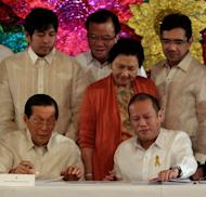 "Philippine President Beningno Aquino (R) and senate president Juan Ponce Enrile is seen signing the ""sin tax"" law in this photo provided by the Malacanang Photo Bureau on December 20, 2012. The new taxes aim to raise 33 billion pesos this year alone"