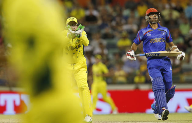 Afghanistan's Nawroz Mangal  completes a run as Australian wicketkeeper Brad Haddin cups his hands to catch the ball during their Cricket World Cup Pool A match in Perth, Australia, Wednesday, March 4