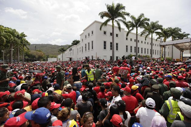 A crowd waits to enter the military academy where the body of Venezuela's late President Hugo Chavez lies in state in Caracas, Venezuela, Thursday, March 7, 2013. While Venezuela remains deeply divide