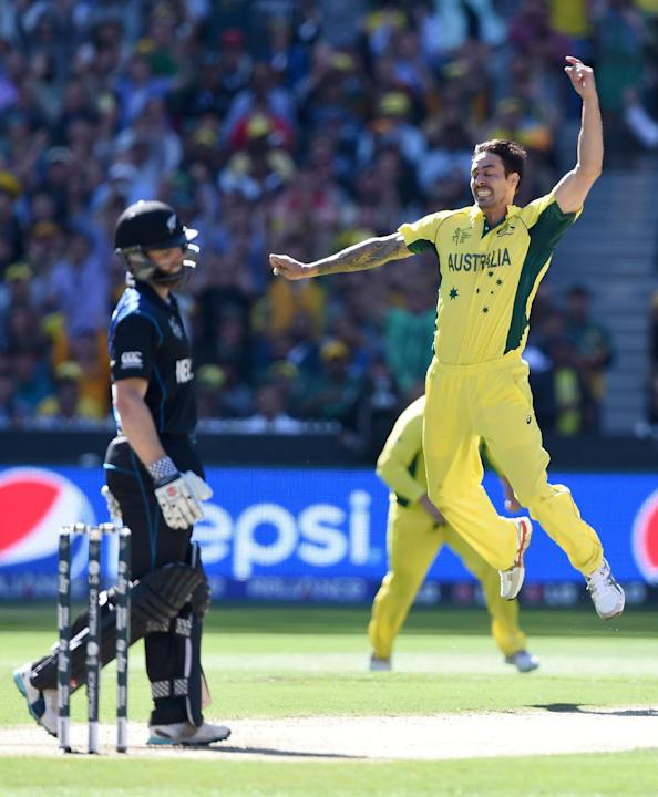Australia's Mitchell Johnson, right, celebrates after taking the wicket of New Zealand's Kane Williamson, left, during the Cricket World Cup final in Melbourne, Australia, Sunday, March 29, 2015.