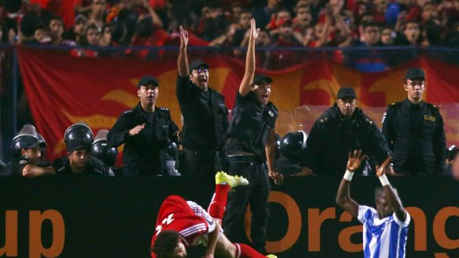 Egypt's riot police officers react after Hossam Ghaliy of Egypt's Al Ahly was tackled by Jules Cesar of Ivory Coast's Sewe Sport during their African Confederations Cup final soccer match at Cairo stadium