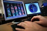 File picture shows a police officer investigating a paedophile website. Hundreds of paedophiles prowling on the Internet have been identified in an operation in 141 countries, Austrian federal police said Wednesday