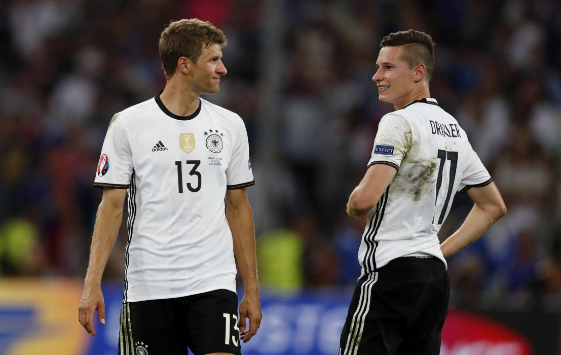 Germany's Thomas Muller and Julian Draxler react at the end of the match