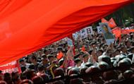 Demonstrators surge towards police lines during a large-scale anti-Japanese protest outside the Japanese Embassy in Beijing on September 15. Shares in Japan Airlines slumped 4.29 percent Friday, two days after relisting, as it said it would slash flights to China amid a territorial row over a group of islands between Tokyo and Beijing