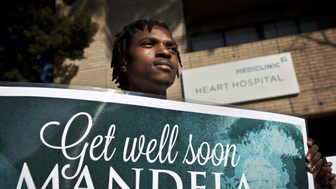 A group of wellwishers hold up get-well placards outside the entrance to the Mediclinic Heart Hospital where former South African President Nelson Mandela is being treated in Pretoria, South Africa, Sunday, June 16, 2013. South Africa's president says that Nelson Mandela is seeing sustained improvement from the recurring lung infection that is forcing him to spend a ninth day in the hospital. (AP Photo/Ben Curtis)