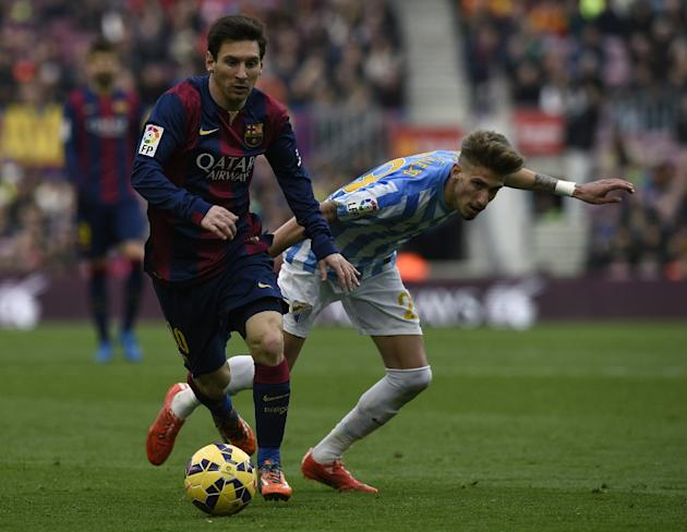 Barcelona's Lionel Messi (L) fights for the ball with Malaga's Samuel Castillejo during their Spanish La Liga match, at the Camp Nou stadium in Barcelona, on February 21, 2015