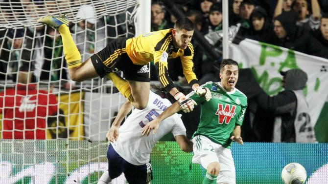 Olympique Lyon's Gorgelin makes a save in front of Bisevac and St Etienne's Hamouma during their French Ligue 1 soccer match at the Geoffroy Guichard stadium in Saint-Etienne