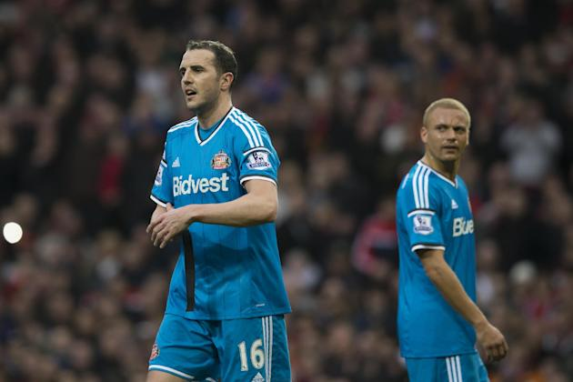 Sunderland's John O'Shea, left, removes his captain's armband as teammate Wes Brown is mistakenly sent off by referee  Roger East for a foul on Manchester United's Radamel Falcao durin