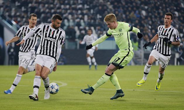 Manchester City's Kevin De Bruyne has a shot at goal as Juventus' Andrea Barzagli looks on