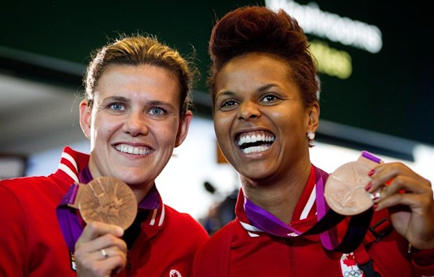 Canadian women's soccer team captain Christine Sinclair, left, and goalkeeper Karina LeBlanc show off their bronze medals from the London Olympics upon arrival from London at Vancouver International Airport in Richmond, B.C., on August 13, 2012. Veteran Canadian goalkeeper Karina LeBlanc says she will retire from international soccer after the Women's World Cup. THE CANADIAN PRESS/Darryl Dyck