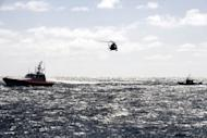 File photo of a boat full of would be immigrants being escorted by an Italian Guardia di Fininanza helicopter and an Italian Coast Guard patrol vessel before reaching the port of Lampedusa in March 2011. Lampedusa, which has a surface area of just 20 square kilometres, is Italy's southernmost point and is closer to North Africa than to the Italian mainland