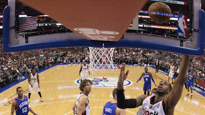 Portland Trail Blazers' LaMarcus Aldridge, right, shoots as he gets past Philadelphia 76ers' Spencer Hawes during the first half of an NBA basketball game on Saturday, Dec. 14, 2013, in Philadelphia