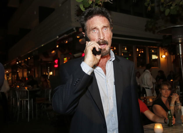 Anti-virus software founder John McAfee talks on his mobile phone as he walks on Ocean Drive in the South Beach area of Miami Beach, Fla., on his way to dinner Wednesday, Dec 12, 2012. McAfee arrived