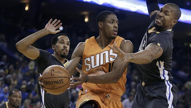 Phoenix Suns' Brandon Knight, center, passes between Golden State Warriors' Shaun Livingston, left, and David West (3) during the first half of an NBA basketball game Saturday, Dec. 3, 2016, in Oakland, Calif. (AP Photo/Ben Margot)