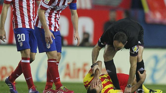 Barcelona's Javier Mascherano from Argentina, bottom, holds his face as the referee helps him after a foul during a Spanish La Liga soccer match between Atletico de Madrid and FC Barcelona at the Vicente Calderon stadium in Madrid, Spain, Saturday, Jan. 11, 2014
