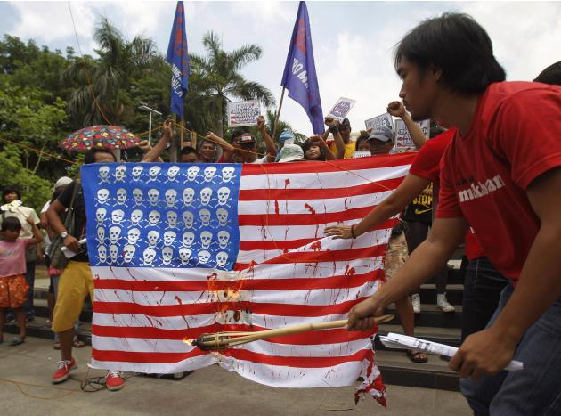 A protester burns a mock U.S. flag during a protest in Manila
