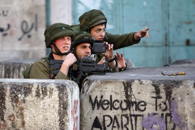 Israeli soldier uses his mobile to take pictures during clashes with Palestinian stone-throwers in the West Bank city of Hebron