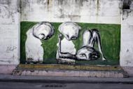In this Feb. 12, 2017 photo, the work of urban artist Yulier P. adorns a wall on a street in Old Havana, Cuba. The 27-year-old artist, whose full name is Yulier Rodríguez, has not catalogued his paintings, which typically take about 40 minutes to complete, but estimates that he has done around 150, mostly in Havana. (AP Photo/Ramon Espinosa)