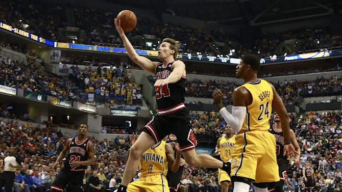 Chicago Bulls forward Mike Dunleavy (34) shoots after getting past Indiana Pacers forward Paul George (24) in the first half of an NBA basketball game in Indianapolis, Friday, March 21, 2014