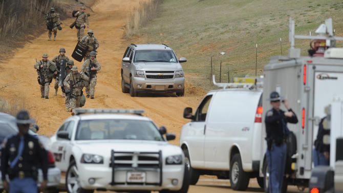Heavily armed men move away from the suspects home at the scene of a Dale County hostage scene in Midland City, Ala. on Wednesday Jan. 30, 2013. Authorities were locked in a standoff Wednesday with a gunman authorities say on Tuesday intercepted a school bus, killed the driver, snatched a 6-year-old boy and retreated into a bunker at his home in Alabama. (AP Photo/Montgomery Advertiser, Mickey Welsh)  NO SALES