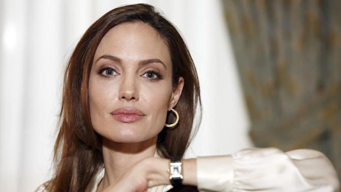 "FILE-  In this Saturday, Dec. 3, 2011 file photo, actress Angelina Jolie poses for a portrait to promote her directorial debut of the film ""In the Land of Blood and Honey""  in New York. Jolie authored an op-ed for Tuesday's May 14, 2013 New York Times where she writes that in April she finished three months of surgical procedures to remove both breasts as a preventive measure. She says she's kept the process private but is writing about it now with hopes she can help other women. (AP Photo/Carlo Allegri, File) ITALY OUT"