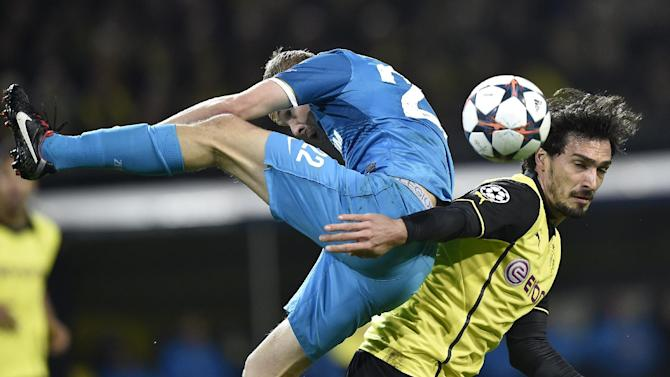 Dortmund's Neven Subotic of Serbia, right, and Zenit's Aleksandr Anyukov, left, challenge for the ball during the UEFA Champions League last 16 second leg soccer match between Borussia Dortmund and FC Zenit in Dortmund, Germany, Wednesday, March 19, 2014