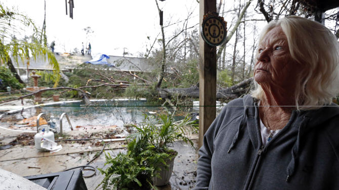 Dot Peek, looks at the damage Sunday's tornado caused her and her daughter's home next door in Hattiesburg, Miss., Monday, Feb. 11, 2013. The tornado damaged both her roof and that of her daughter's house. Peek said she recently had the swimming pool refinished and now she has two trees in the pool as result from the strong winds that caused damage throughout the South Mississippi college town. (AP Photo/Rogelio V. Solis)