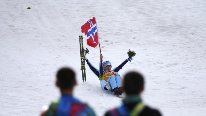 Krog and his compatriot Klemetsen celebrate by sliding after the flower ceremony for the Nordic Combined team Gundersen event of the Sochi 2014 Winter Olympic Games