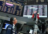 """A trader works on the floor of the New York Stock Exchange May 8 in New York City. JPMorgan Chase's shares were pummeled and politicians blasted its CEO Jamie Dimon after the bank reported a shock $2 billion derivatives loss that even the pugnacious chief executive called """"egregious."""""""
