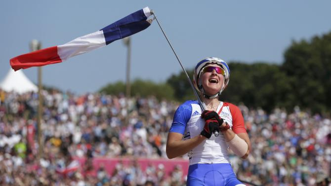 France's Julie Bresset celebrates after winning gold during the women's Cross-country mountain bike cycling event at Hadleigh Farm during the London 2012 Olympic Games