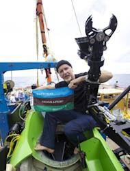 "Filmmaker and National Geographic Explorer-in-Residence James Cameron holds the National Geographic Society flag after he successfully completed the first ever solo dive to the Mariana Trench, the deepest part of the ocean, on Monday. Speaking after the mission, the filmmaker-explorer described a barren ""completely alien world"" on the ocean floor, not unlike the surface of the moon"