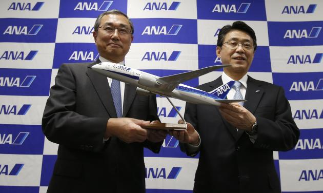 ANA Holdings Inc's President Ito stands next to incoming President Katanozaka as they pose with a model of a Boeing 787 Dreamliner aircraft during a news conference at the company headquarters in