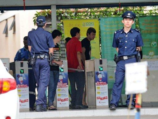 Policemen stand by the entrance to a foreign workers' dormitory in Singapore on November 26. More than 100 mainland Chinese bus drivers in Singapore refused to work in a rare case of labour mass action in the city-state