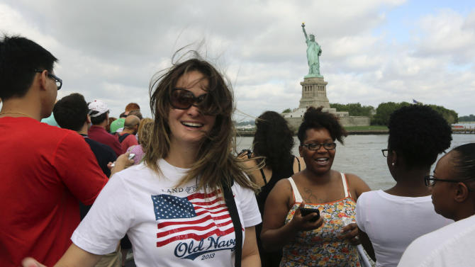 Visitors to fhe Statue of Liberty take photos as they arrive on the first tourist ferry to leave Manhattan, Thursday, July 4, 2013, in New York. The Statue of Liberty finally reopened on the Fourth of July months after Superstorm Sandy swamped its island in New York Harbor as Americans across the country marked the holiday with fireworks and barbecues. (AP Photo/Mary Altaffer)