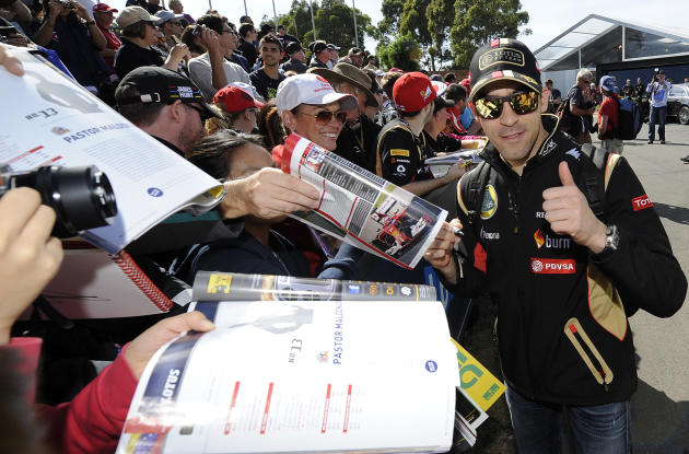 Lotus driver Pastor Maldonado of Venezuela thumbs up as he signs autographs ahead of the Australian Formula One Grand Prix at Albert Park in Melbourne, Australia, Thursday, March 13, 2014. (AP Photo/A