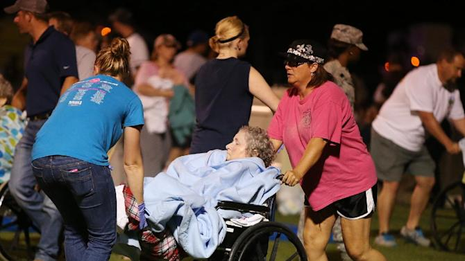 An elderly person is assisted at a staging area at a local school stadium  following an explosion at a fertilizer plant Wednesday, April 17, 2013, in West, Texas. An explosion at a fertilizer plant near Waco caused numerous injuries and sent flames shooting high into the night sky on Wednesday. (AP Photo/ Waco Tribune Herald, Rod Aydelotte)