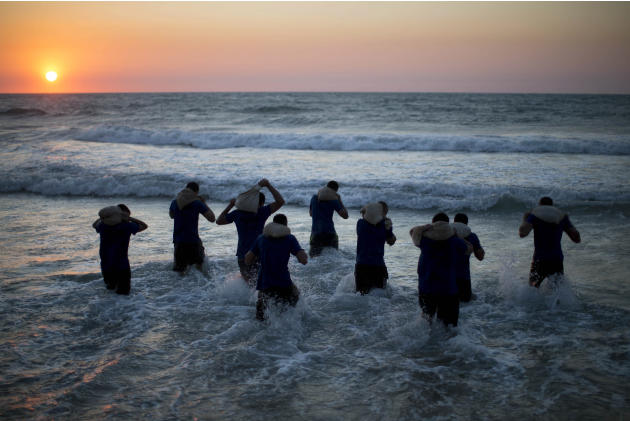 AP10ThingsToSee - Israeli high-school seniors preparing to join the Israeli military later this year walk into the sea carrying weighted bags during privately run military combat fitness training in S