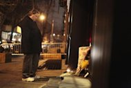 A man mourns in front of flowers placed in memory of actor Philip Seymour Hoffman outside the apartment where Hoffman was found dead in Manhattan, New York February 2, 2014. REUTERS/John Taggart