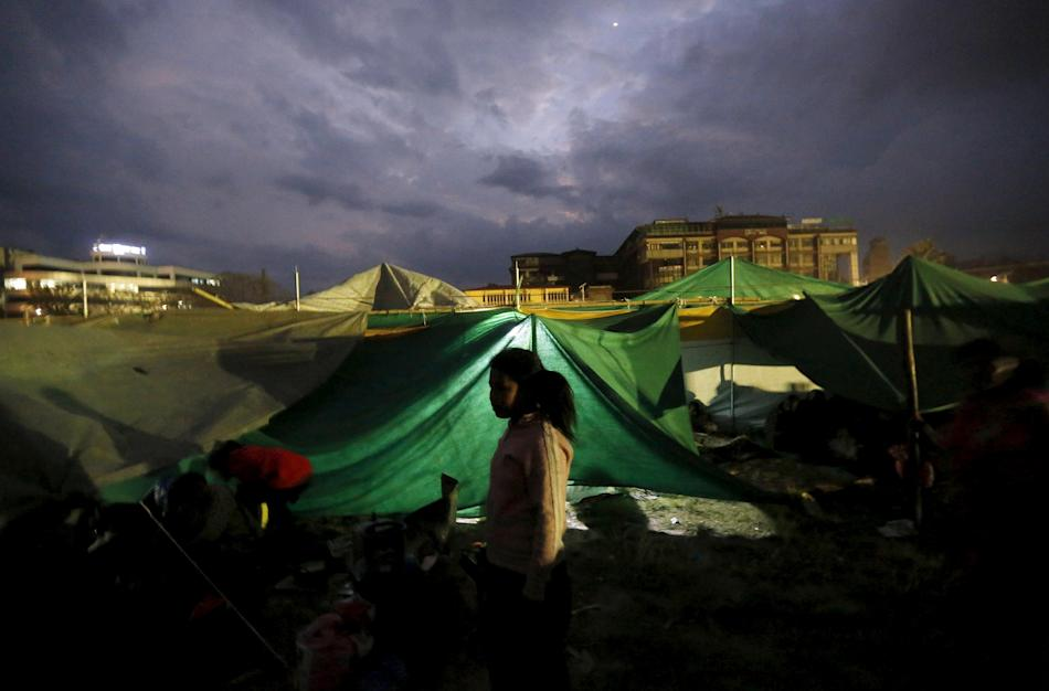 A girl stands outside her makeshift shelter at an open ground after an earthquake in Kathmandu