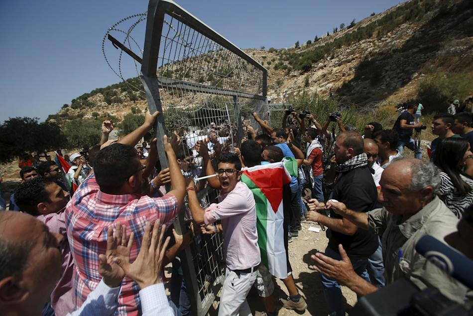 Palestinians remove a gate, part of Israel's controversial barrier, during a protest in the West Bank city of Beit Jala